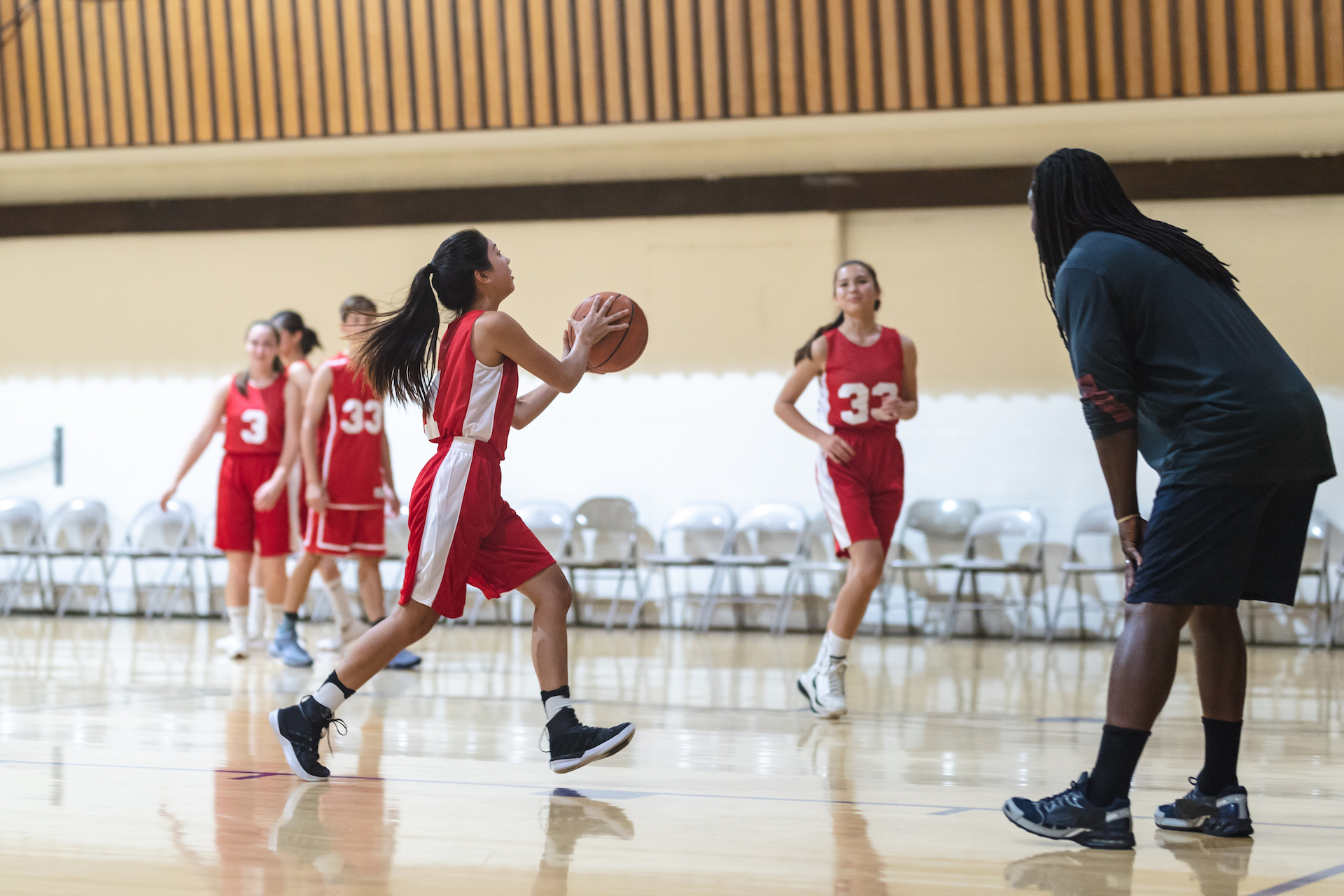 Coach has his co-ed basketball team run layup drills during practice. One girl is dribbling and about to pass to her teammate.