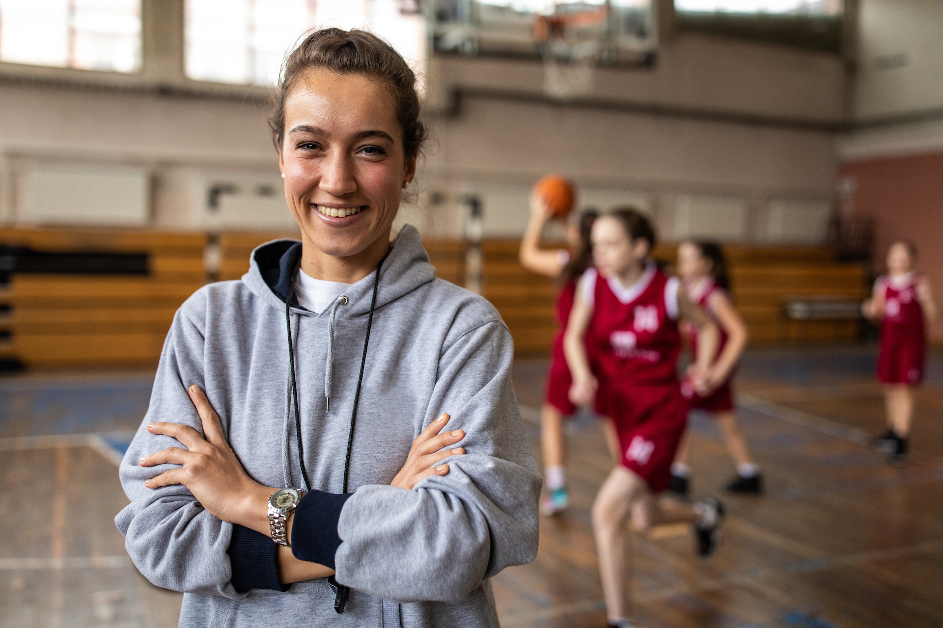 Young beautiful female basketball coach standing in school gym with crossed arms , looking at camera and smiling