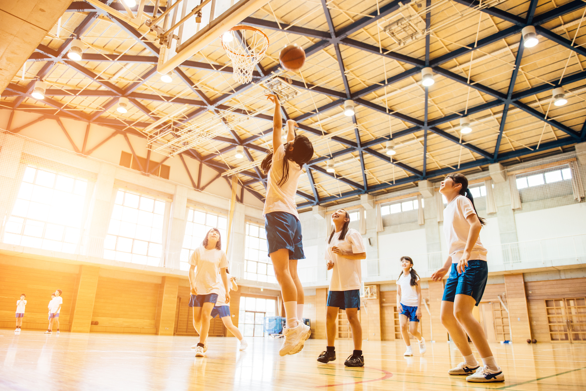 Japanese Junior High School girl friends playing basketball in the School GYM.